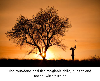 The mundane and the magical: child, sunset and model wind turbine